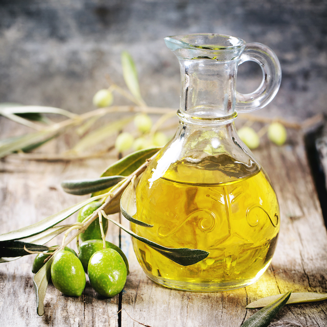 Battle of olive oil with olive branch over wooden table. Square image, selective focus