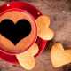 Cup of coffee and heart shape cookies on the table