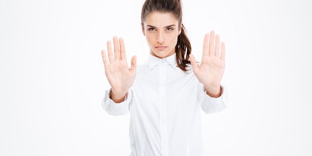 Serious beautiful young businesswoman showing stop gesture with both hands