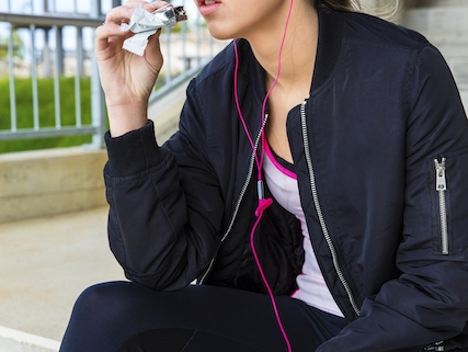Sporty Woman Eating Protein Bar While Listening Music On Steps