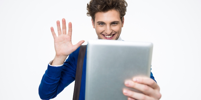 Smiling young man with curly hair using tablet computer