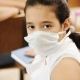 Schoolgirl with medicine mask on face, in classroom, against: virus, ill, epidemic, plague, flu