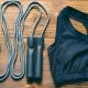 Sports bra and jump rope on wooden background. The view from the top.