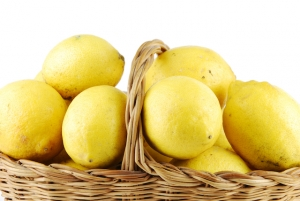 close-up of lemons in a traditional wicker basket isolated on white background