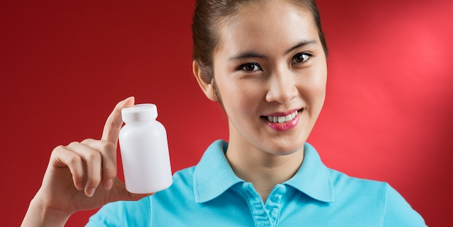 Close-up portrait of a young sportswoman with vitamins in hands isolated on red