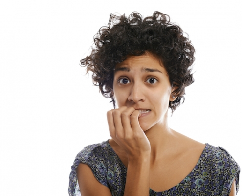 portrait of worried and stressed hispanic girl biting nails and looking at camera on white background