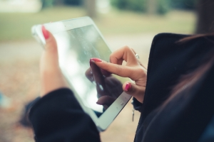 close up of woman hands using tablet outdoor - connection wireless social network internet online