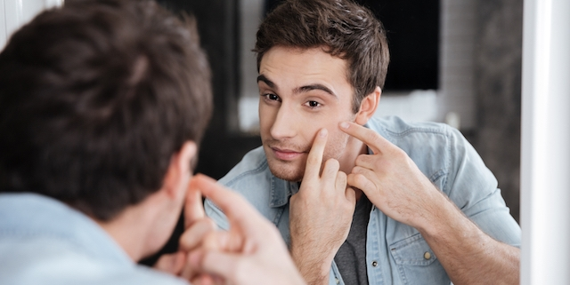 Close up portrait of a man looking at himself in a mirror and squeezing his pimples