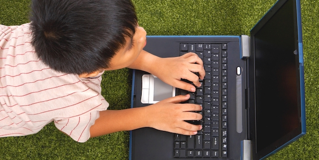 Young Kid Using His Notebook Computer For Study And Fun