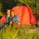 Camping couple sitting by tent and enjoying the sunset