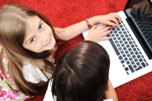 Little girl and boy lying with laptop at home on the ground