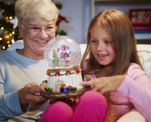 Senior woman with granddaughter holding a christmas decoration