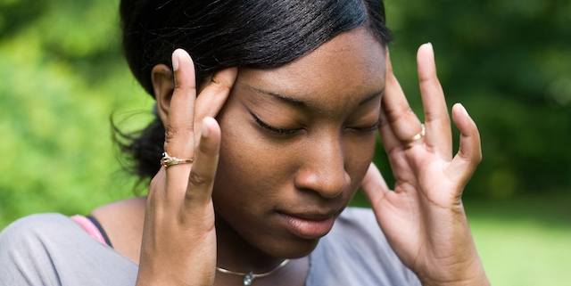 This young woman is experiencing intense stress or pain from a splitting headache.