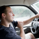 Interior view of a young man driving a van or truck. Shallow depth of field.