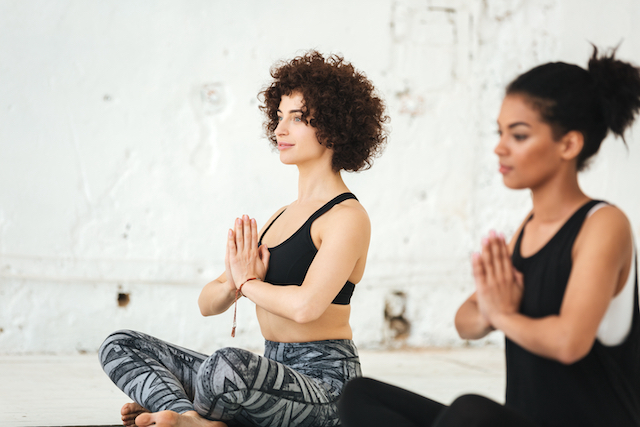 Group of women sitting on a yoga mats and meditating in a studio