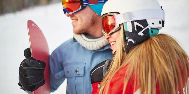 Young female and male snowboarders in winter activewear