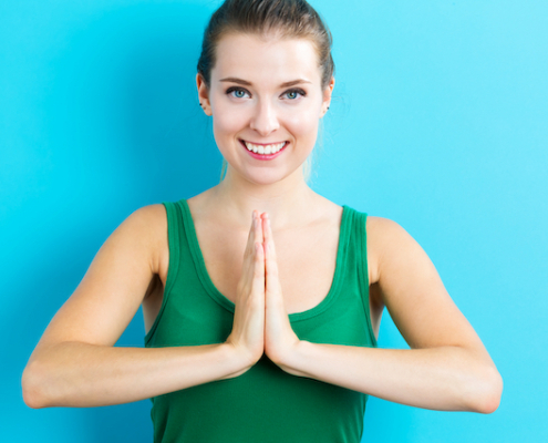 Happy young woman practicing meditation on blue background