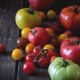 Assortment of big RAF red and green and cherry tomatoes red, yellow and orange over old wooden table. Dark rustic style. Day light.