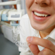 Close-up shot of man with big smile holding mouth guard or orthodontic retainers in dental office